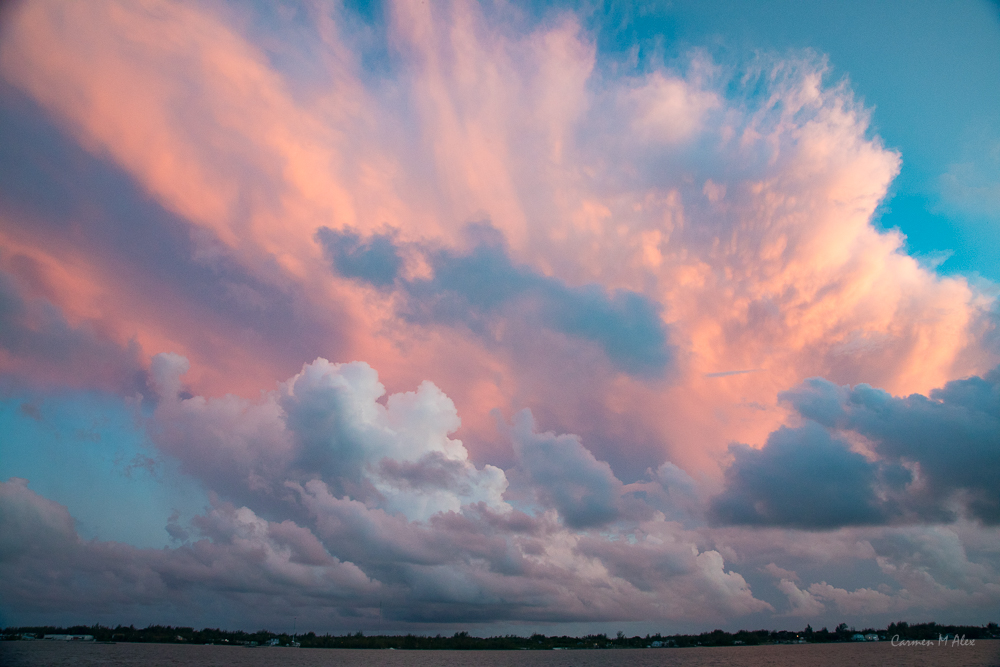 Orange, sunlit cumulunimbis cloud in back, pinkish stratocumulus below.